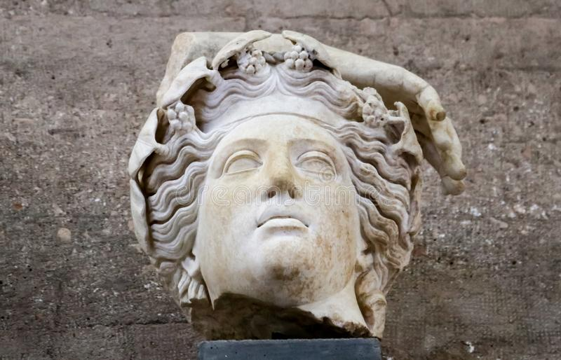 Fragment of roman statue - god from ancient Corinth Greece with flowers or grapes in wavy hair and part of a hand. Head - Fragment of roman statue - god from stock image