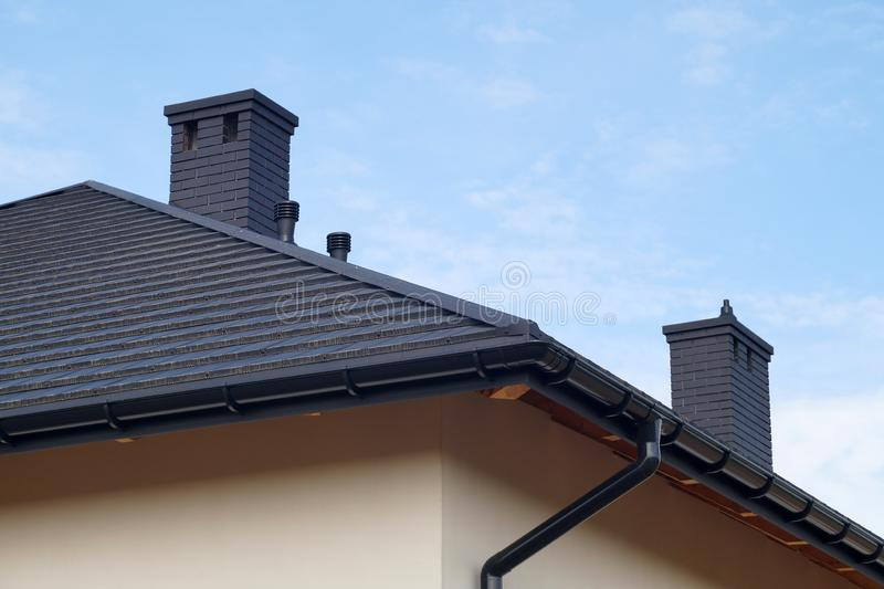 A fragment of the roof made of metal roof tiles, new chimneys. A newly built residential house stock images