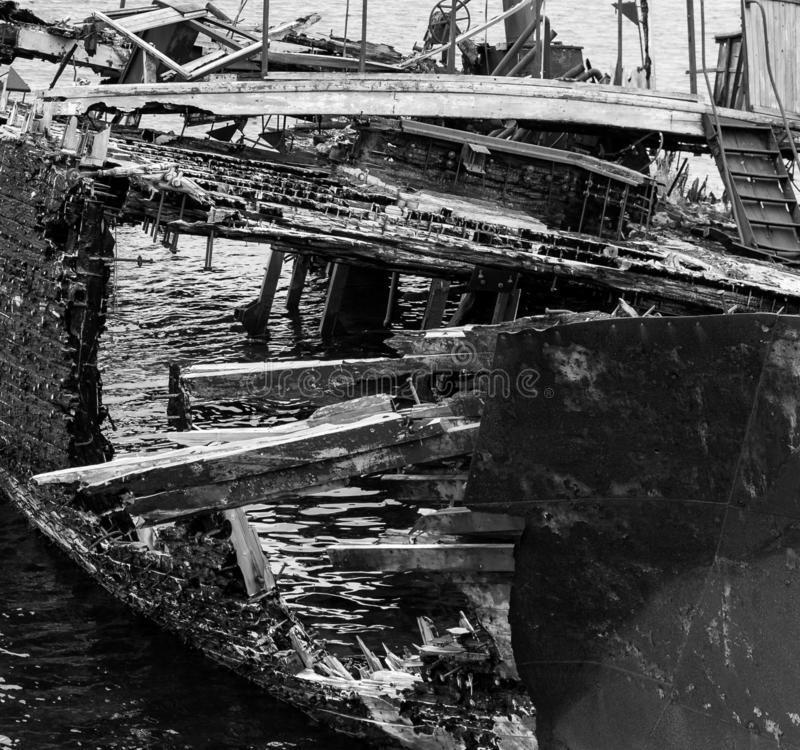 Fragment of rotting, abandoned ship on the shore, a symbol of decadence and degradation, a monochrome image. Barents Sea, Russia royalty free stock photography