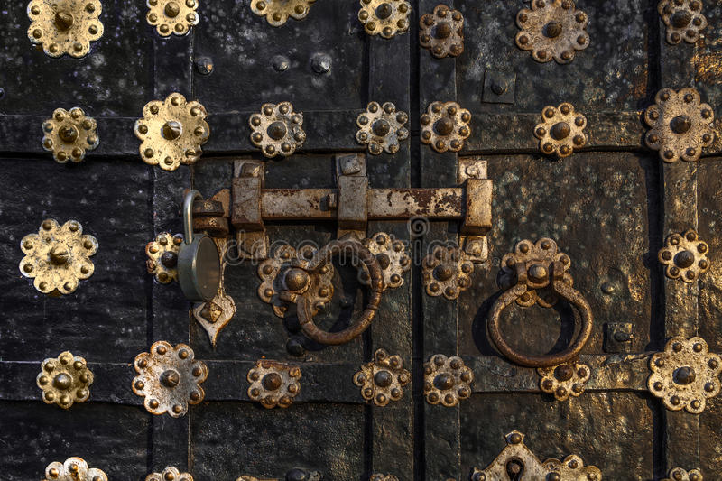 Fragment of shod iron gate. Fragment of old church shod iron gate with the modern padlock stock photos