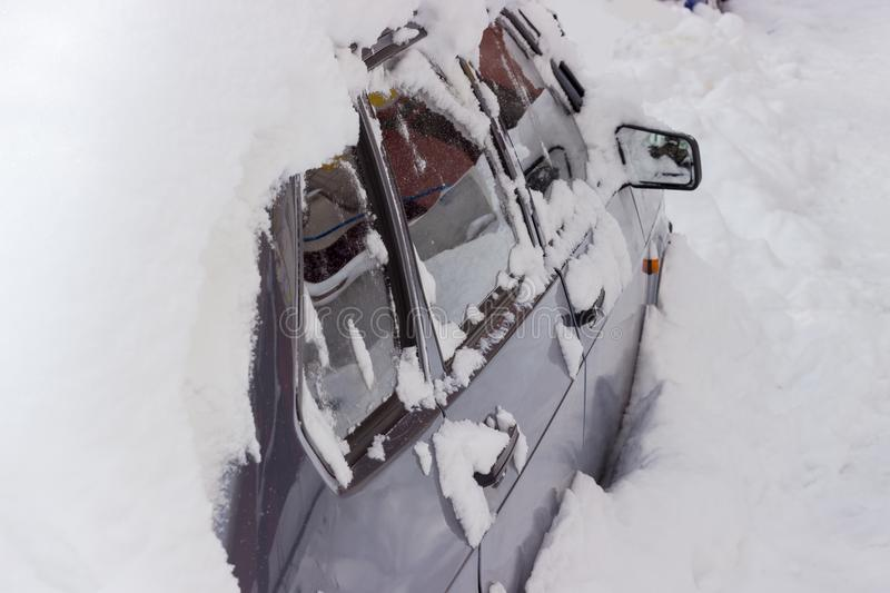 Fragment of the side part of the heavily snowbound car royalty free stock image