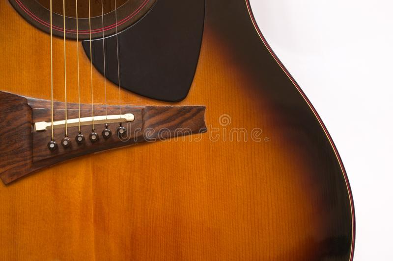 Fragment of an acoustic guitar shown frontally. Fragment of a six-string acoustic guitar on a white background in natural light stock photography