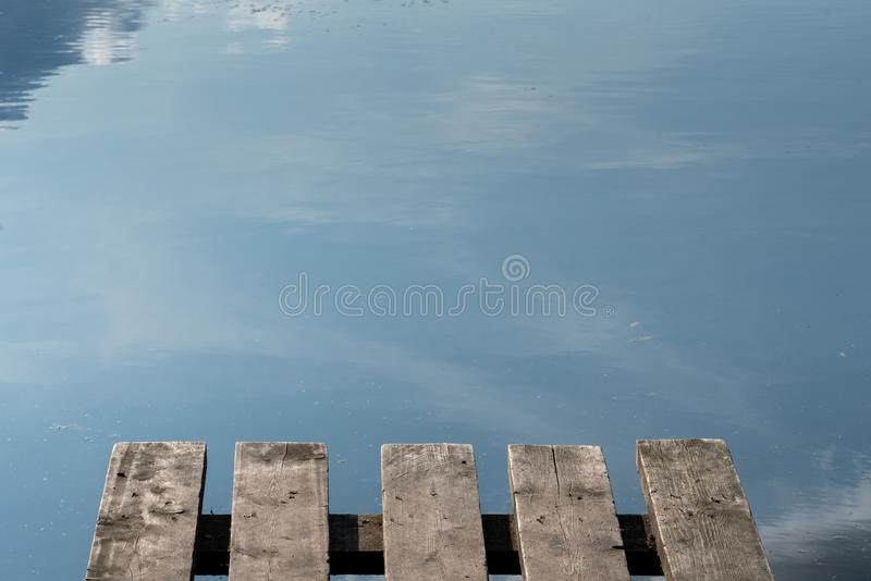 Fragment of a small wooden jetty on the background of the lake. Reflection of the sky in the lake royalty free stock photos