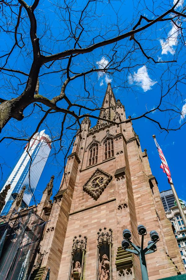 Fragment of St. Paul`s Church in Trinity Church of Wall Street with American flag, tree and skyscraper. USA royalty free stock photos