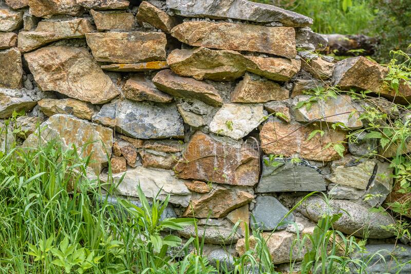 Fragment of a stone wall and grass. Fragment of a stone wall and green grass royalty free stock photos