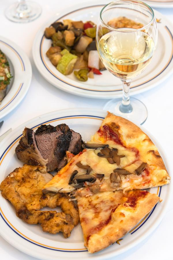 Fragment of table served with slices of pizza, meat and white wine in glass. Fragment of a table served with slices of pizza, meat and white wine in a wine glass stock photos