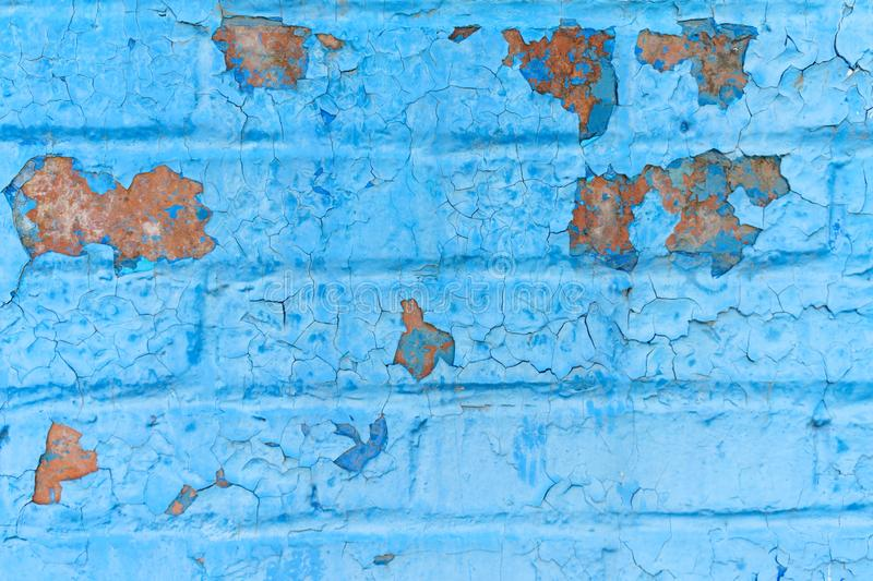 Old grunge brick wall of a background or texture painted in blue paint that cracked under the influence of time and weather royalty free stock photography