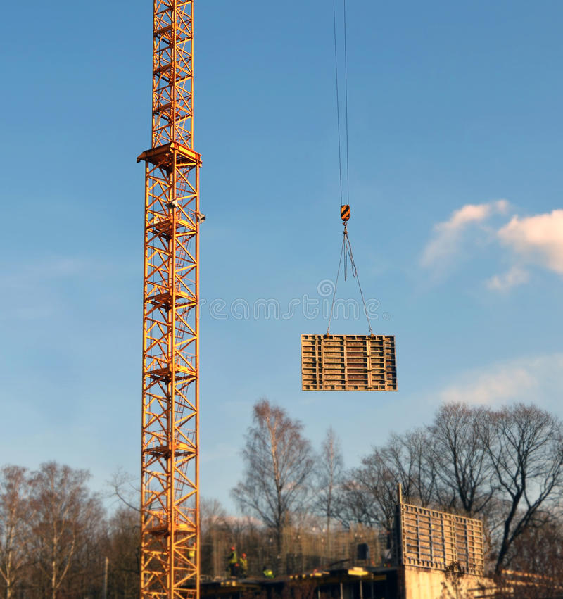 Fragment of a tower of a lifting tower crane and the moved freight. Fragment of a tower of a lifting tower crane which moves the construction block on blur a royalty free stock photography
