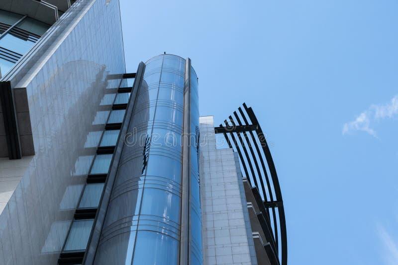 Fragment van de moderne high-rise bouw van glas en beton tegen een blauwe hemel royalty-vrije stock afbeeldingen