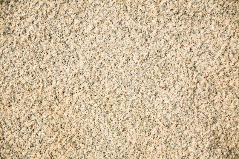 Fragment van een beige graniet die plak onder ogen zien Onbehandelde gewaagde steenoppervlakte van natuurlijk beige graniet stock afbeeldingen
