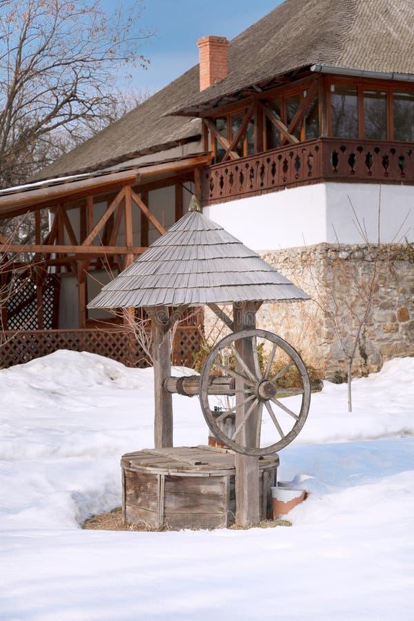 Fragment van een dorpsbinnenplaats met houten goed en een huis in het Nationale Dorpsmuseum Boekarest, Roemeni? royalty-vrije stock foto's