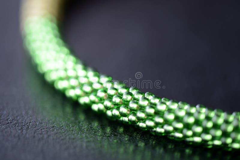 Fragment van een geparelde halsband drie schaduwen van groen op een donkere achtergrond royalty-vrije stock fotografie