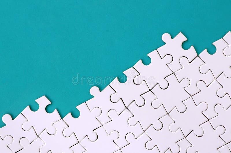 Fragment van een gevouwen witte puzzel op de achtergrond van een blauwe plastic oppervlakte Textuurfoto met exemplaarruimte voor  stock fotografie