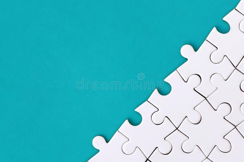 Fragment van een gevouwen witte puzzel op de achtergrond van een blauwe plastic oppervlakte Textuurfoto met exemplaarruimte voor  stock foto