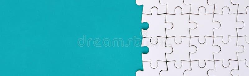 Fragment van een gevouwen witte puzzel op de achtergrond van een blauwe plastic oppervlakte Textuurfoto met exemplaarruimte voor  royalty-vrije stock afbeeldingen