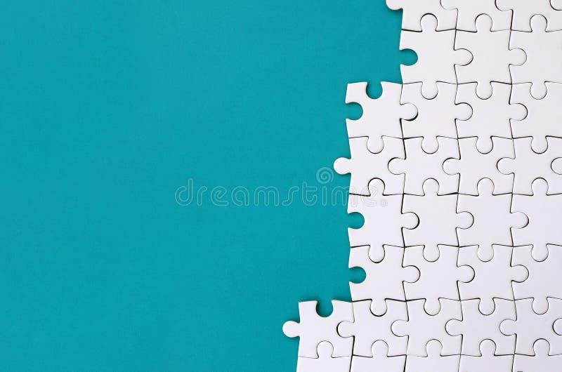 Fragment van een gevouwen witte puzzel op de achtergrond van een blauwe plastic oppervlakte Textuurfoto met exemplaarruimte voor  stock foto's