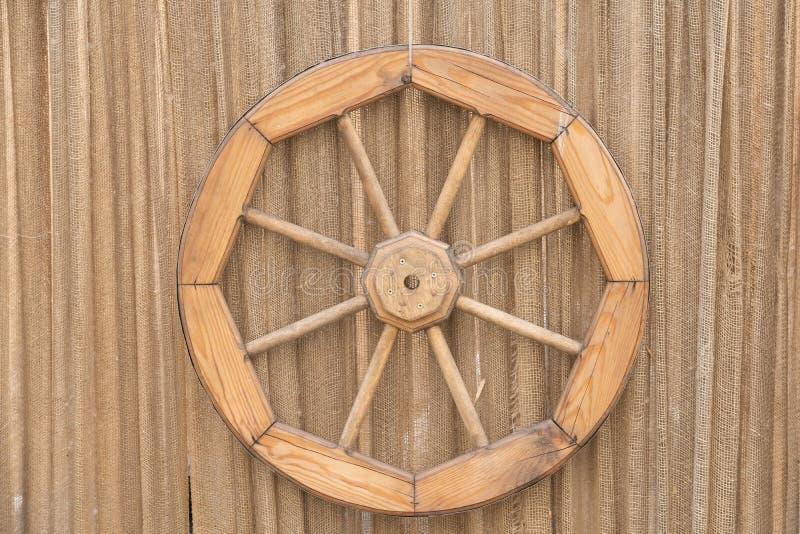 Fragment van een oude muur met een blauwe deur, een oud houten wiel en een rioolbuis royalty-vrije stock foto's