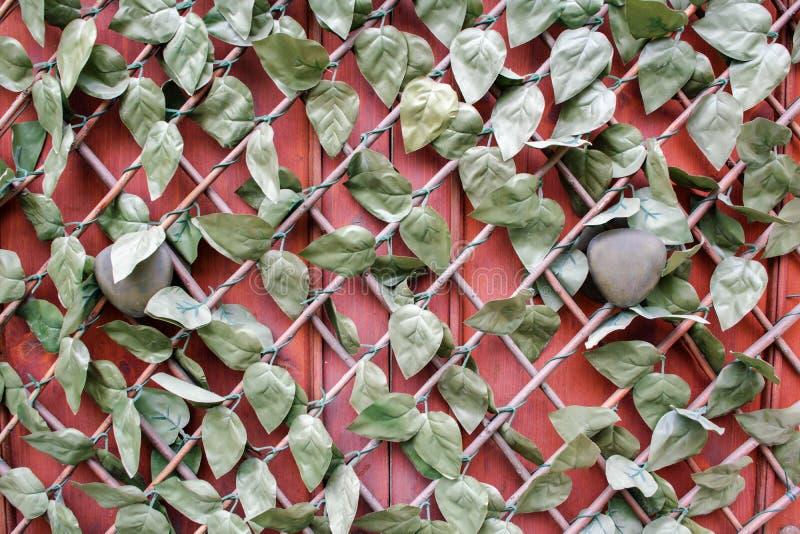Fragment van gesloten houten rode geschilderde die voordeur met de handvatten van de messingsdeur, onder het rooster wordt verbor royalty-vrije stock fotografie