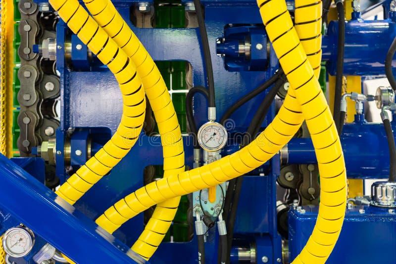 Fragment van krachtig boormateriaal Gele hydraulische slangen, staalkader, drukmaat stock fotografie