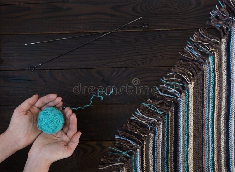Fragment van met de hand gemaakte gebreide stof en vrouwen` s handen met bal royalty-vrije stock afbeelding