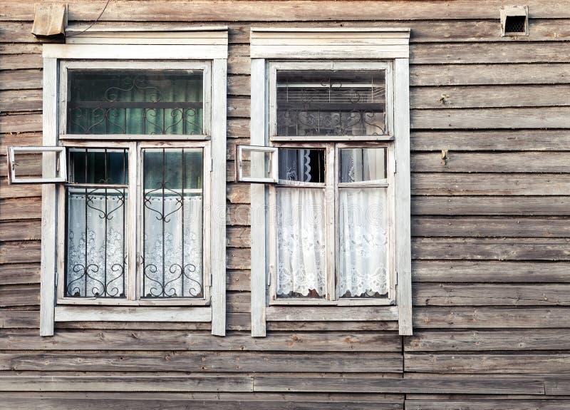 Fragment van oude landelijke houten muur met vensters stock fotografie