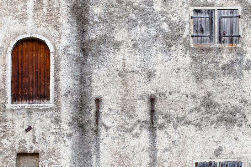 A fragment of a old abandoned house with a closed door and a shuttered blind window royalty free stock photos