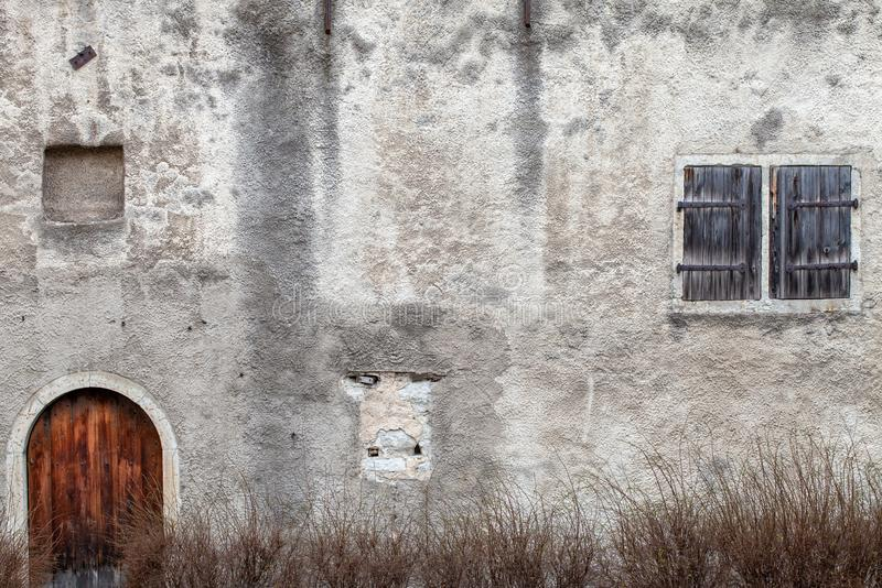 A fragment of a very old house with a closed door and a shuttered blind window stock image