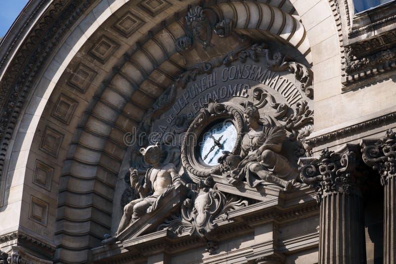 Fragment von Architekturmarksteinen mit einer Uhr und altgriechischen Göttern auf dem Altbau National Banks von Rumänien lizenzfreie stockbilder