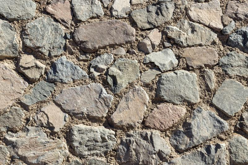 Fragment of a wall from a chipped stone. stone wall background or texture royalty free stock image