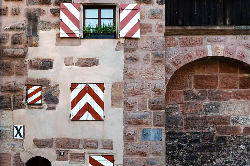 Fragment of the wall of an old building with bright shutters in the city of Nuremberg royalty free stock images