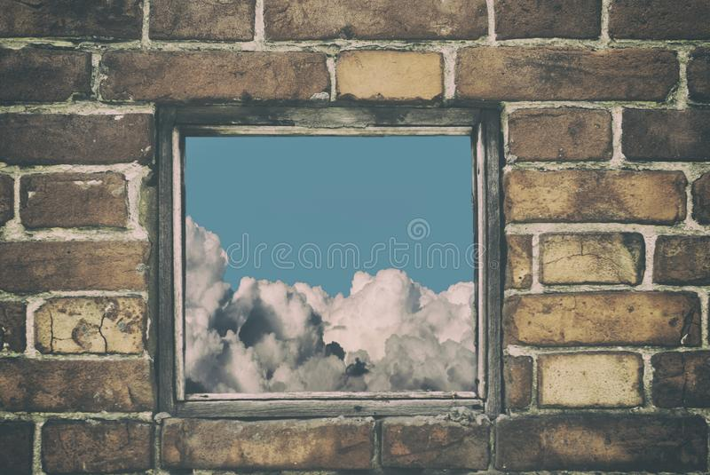 Fragment of the wall of an old house with a bricklaying of red brick and and view from small window with cloud sky royalty free stock photos