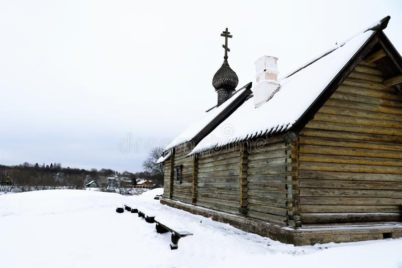Old Russian log church and view of the Volkhov River in winter. stock photos