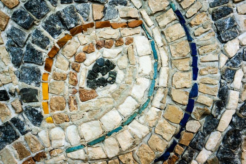 A fragment of the wall of small colored stones. The texture of the stone. Beautiful natural colorful background. Close up royalty free stock image