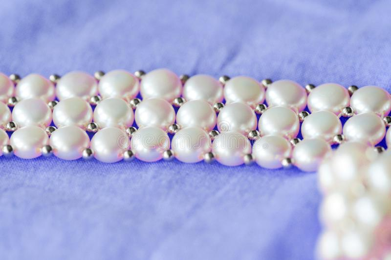 Fragment of a white pearl necklace on a purple color textile background. Close up stock image