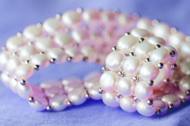 Fragment of a white pearl necklace on a purple color textile background. Close up stock photography