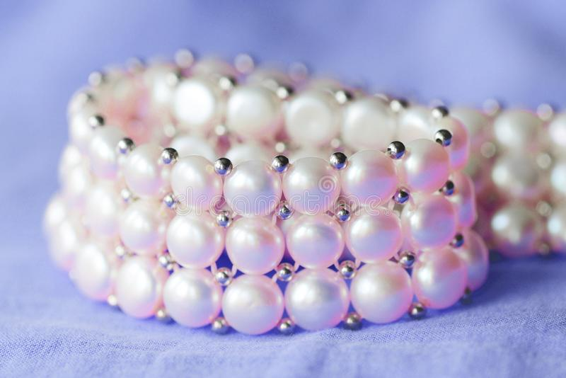 Fragment of a white pearl necklace on a purple color textile background. Close up stock images