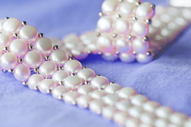 Fragment of a white pearl necklace on a purple color textile background. Close up royalty free stock images