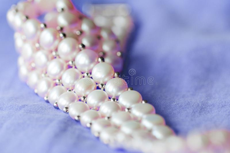 Fragment of a white pearl necklace on a purple color textile background. Close up stock photo