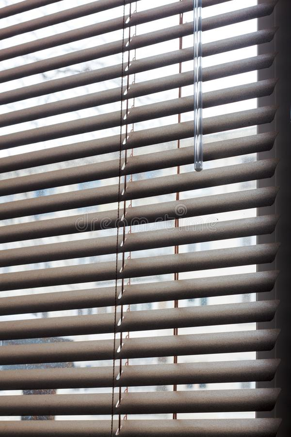 Fragment of the white Venetian blinds with lift cord and turning rod of a manual control on a foreground . royalty free stock images