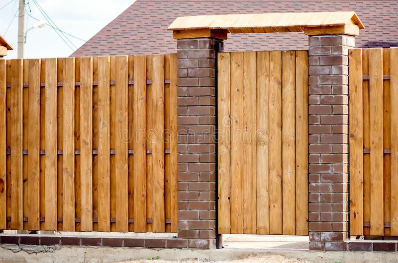 Fragment of a wooden brown modern fence with a wicket, close-up. Modern design ideas of a wooden fence stock image