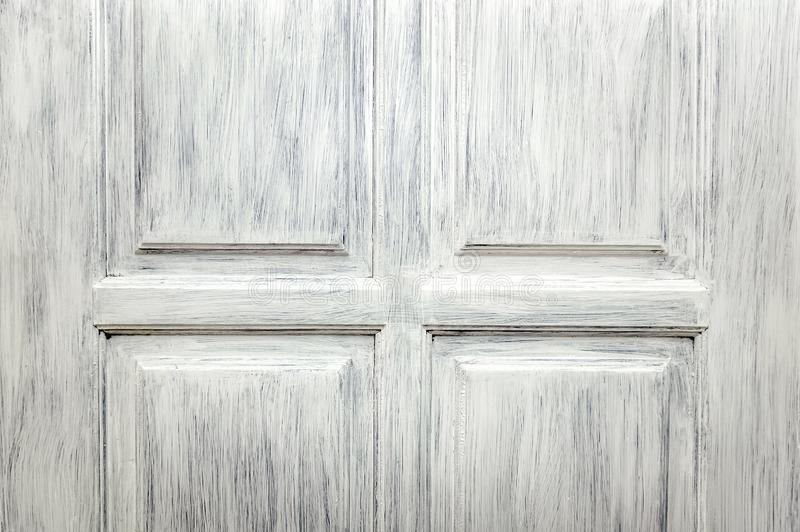 Fragment of a wooden door painted with white paint. Decorative wood texture royalty free stock photography