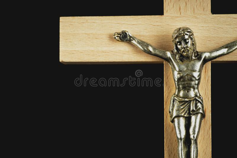 A fragment of a wooden illuminated crucifix against a black back. A fragment of a wooden light-brown illuminated crucifix against a black background royalty free stock photography