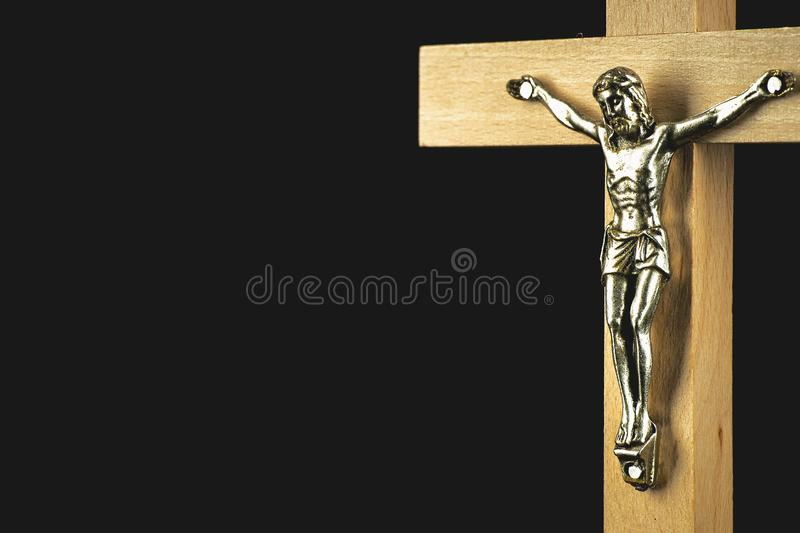 A fragment of a wooden illuminated crucifix against a black back. A fragment of a wooden light-brown illuminated crucifix against a black background stock photo