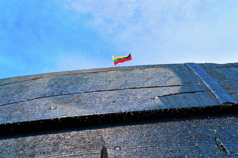 Fragment of wooden ship at Nida resort town near Klaipeda in Neringa on the Baltic Sea at the Curonian Spit in Lithuania. Lithuanian flag royalty free stock images