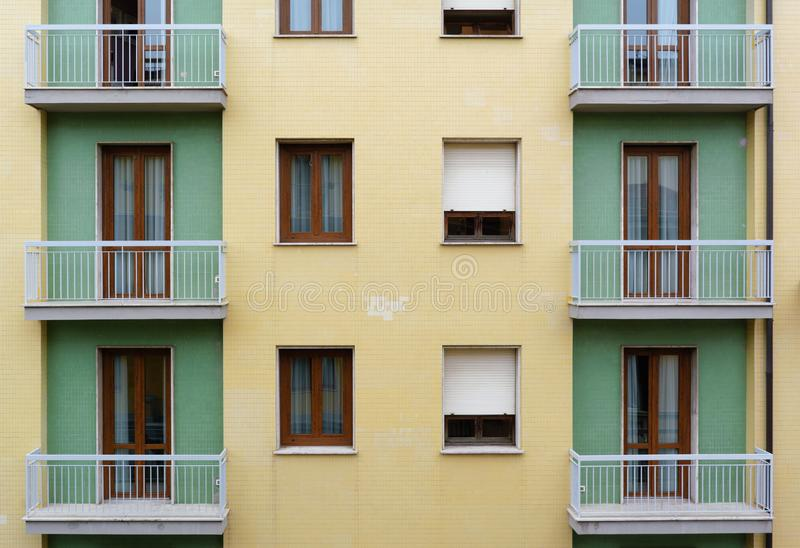 Fragment of yellow and green tiled facade building with balconies royalty free stock photos