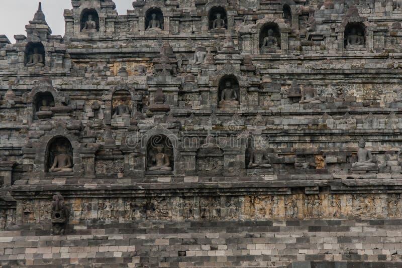 Fragment zewnętrznej świątyni Borobudur z posągami siedzącego Buddy w niszach, Jogyakarta, Jawa Środkowa, Indonezja zdjęcia royalty free