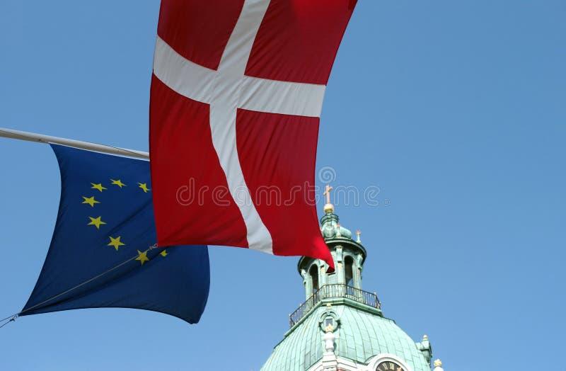 Fragmenten van de vlag van Denemarken en de vlag van de Europese Unie tegen de achtergrond van het blauw stock afbeeldingen