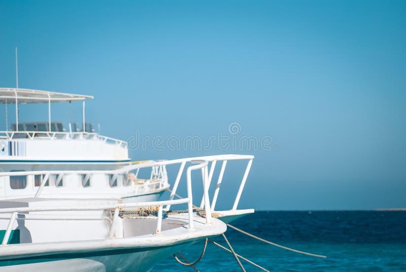 Fragmenten van een wit jacht in de baai van de oceaan of het overzees tegen de blauwe hemel en de waterspiegel Onroerende goedere royalty-vrije stock foto