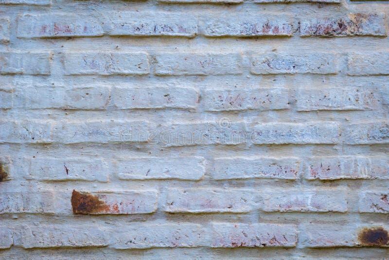 Fragmentera tegelstenväggen som målas av vit med detaljerad textur royaltyfria foton