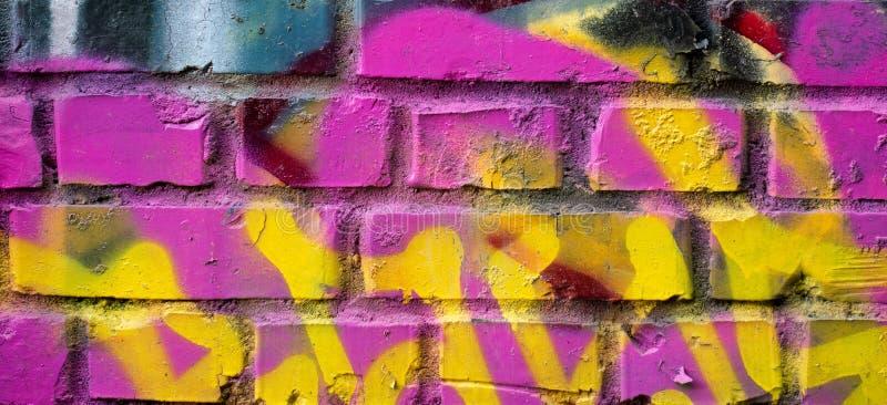 Fragmentet av den färgrika grafittiteckningen som göras med ærosol, målar på en tegelstenvägg fotografering för bildbyråer